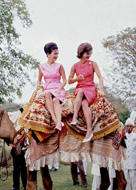 Mrs. Jacqueline Kennedy, the widely traveled wife of Pres. John F. Kennedy, right, perches on camel with her is her sister, Princess Lee Radziwill March 1, 1962, Karachi, Pakistan. Mrs. Kennedy was on a goodwill visit to India and Pakistan. Holding the camel is Bashir Ahmad, left, who won fame when he came to the U.S. last year as a guest of Vice Pres. Lyndon Johnson. (AP Photo)